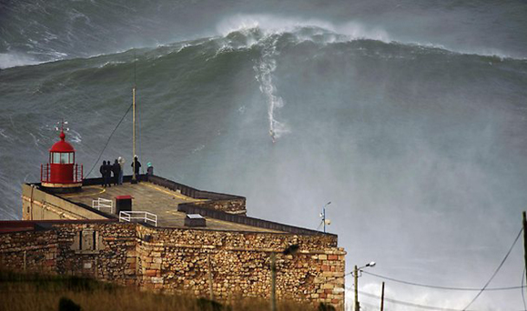 Garrett McNamara surfing a wave estimated to be 100 ft. in Navar, Portugal.