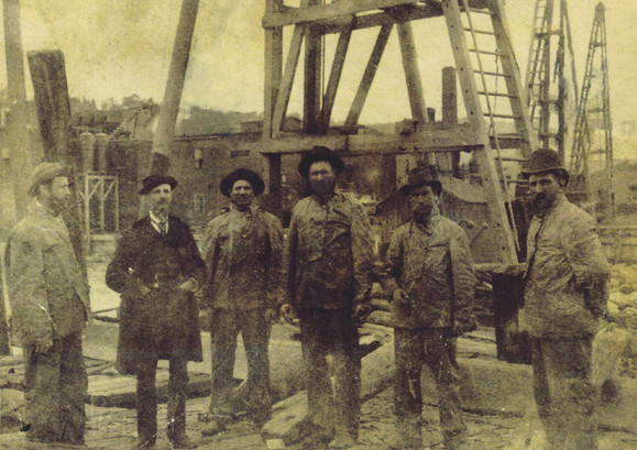Jim Burke on refinery site with his felloe workers. He is the one on the right wearing the derby – the hard hat of his day.