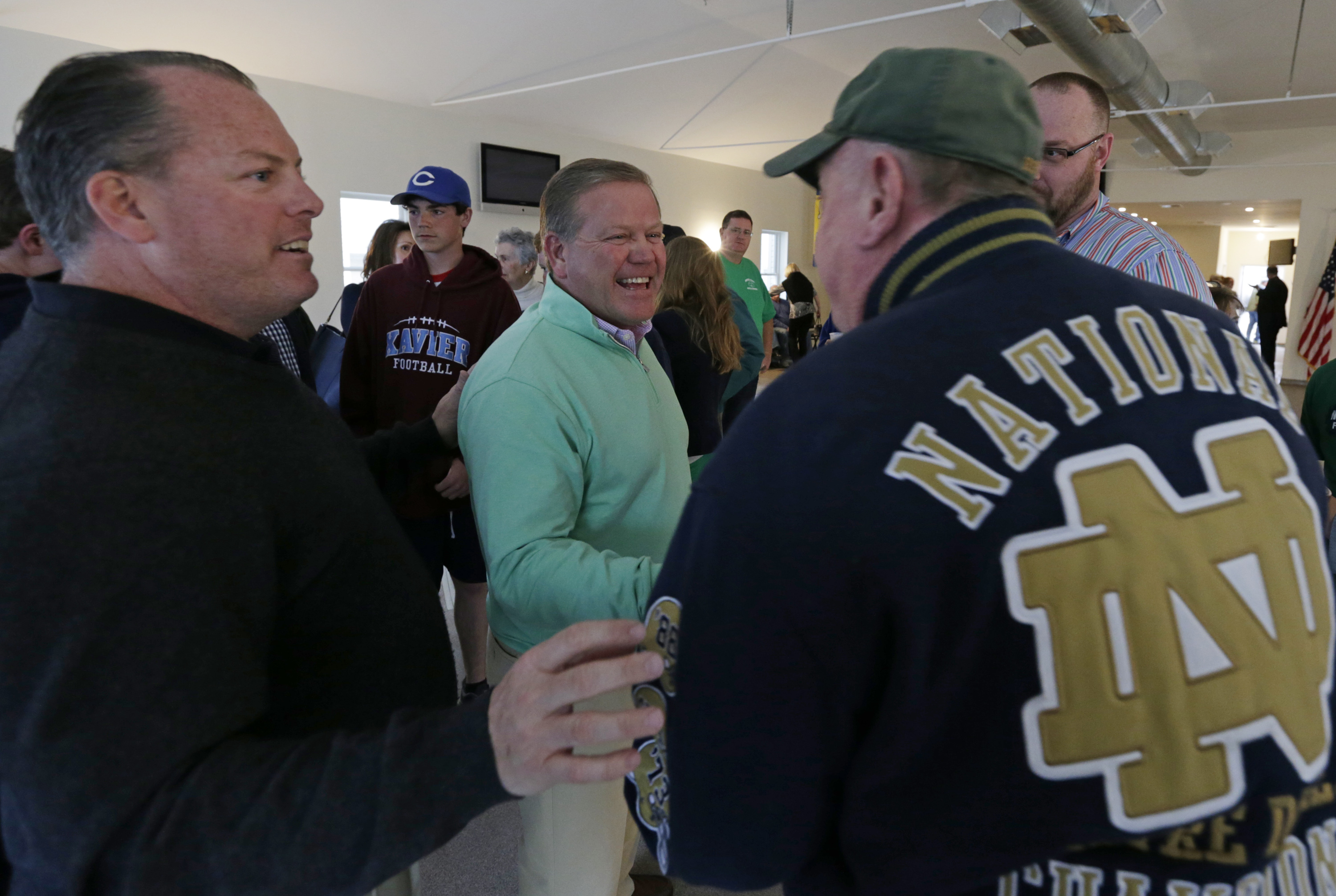 Coach Kelly (center) shakes hands with Pat Mullee (center right) in the new Catholic Club after the ribbon cutting ceremony on April 22. Photo: Peter Foley.