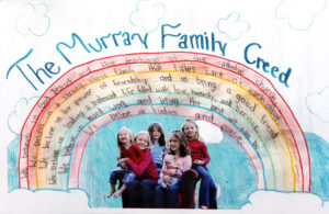 A photo of the six Murray girls with their family creed graced the back of the program for services for the girls' mother and sister who died when a tree fell on their van during a storm.  The girls are from left, Quinn, Jillian, Maeve, Meghan holding Kieran and Sloan, right, who was killed. Photo: Katherine Frey / The Washington Post