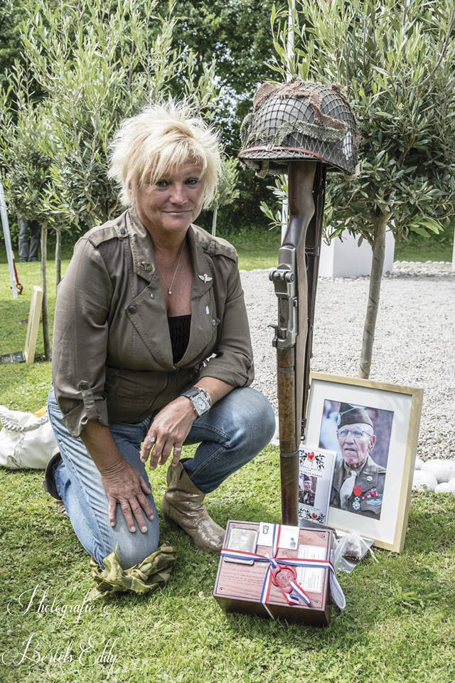 Ellen Womer, daughter of Sgt. Jack Womer, kneels beside the olive tree she planted with her father in his honor in 2013. The D-Day veteran died before the 2014 commemoration. Ellen brought her  father's photo and ashes to the ceremony. The upturned Garand rifle with fixed bayonet and helmet is a tribute Ashe puts beside the tree of each hero who died in the preceding year. Jack Womer's ashes were permanently interred elsewhere in Normandy a few days later.