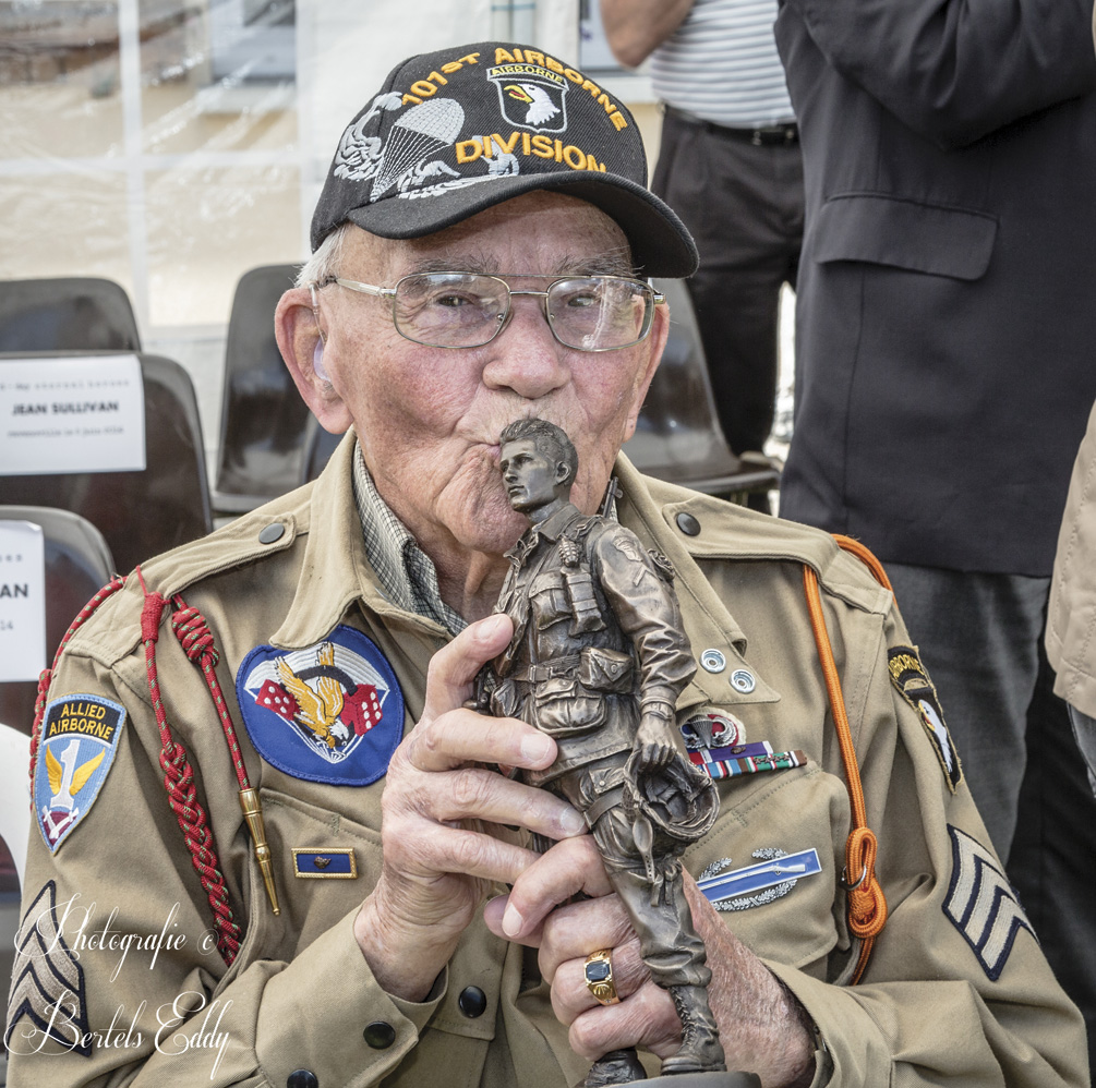 Robert Noody, a  veteran from Star Lake, New York, kisses the paratrooper statuette  he received at the 2014 ceremony in Ravenoville, Normandy.