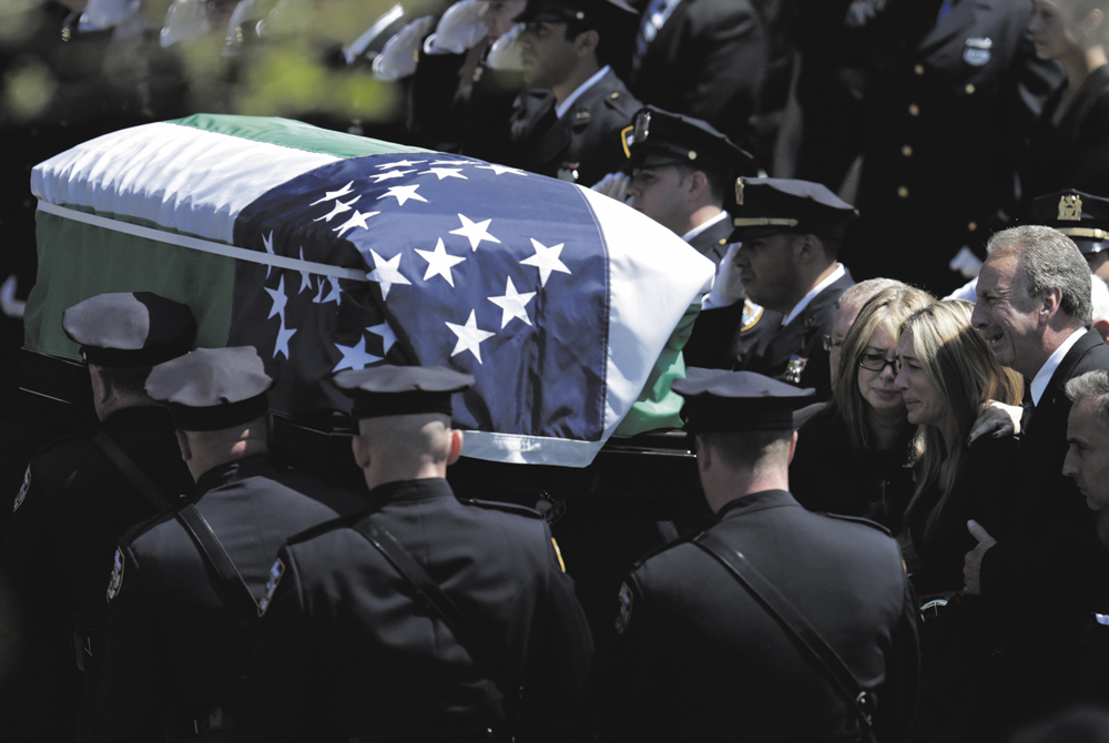 Police officers carry Moore's coffin from  St. James Catholic Church in Seaford, New York.