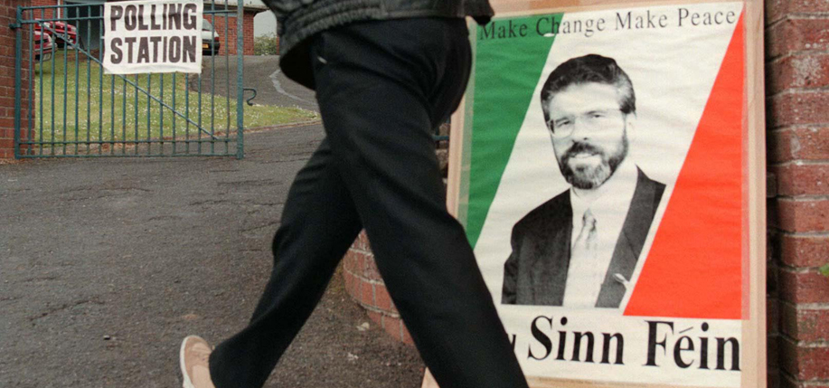 June 25, 1998: A man passes a poster of Sinn Fein leader Gerry Adams as he goes to vote in the Northern Ireland Assembly election today.  PHOTO: CRISPIN RODWELL