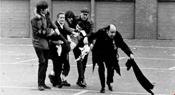 In the photograph that drove Bishop Edward Daly into the public eye,  he leads the wounded Jackie Duddy to safety.  (Photo: Fulvio Grimaldi)