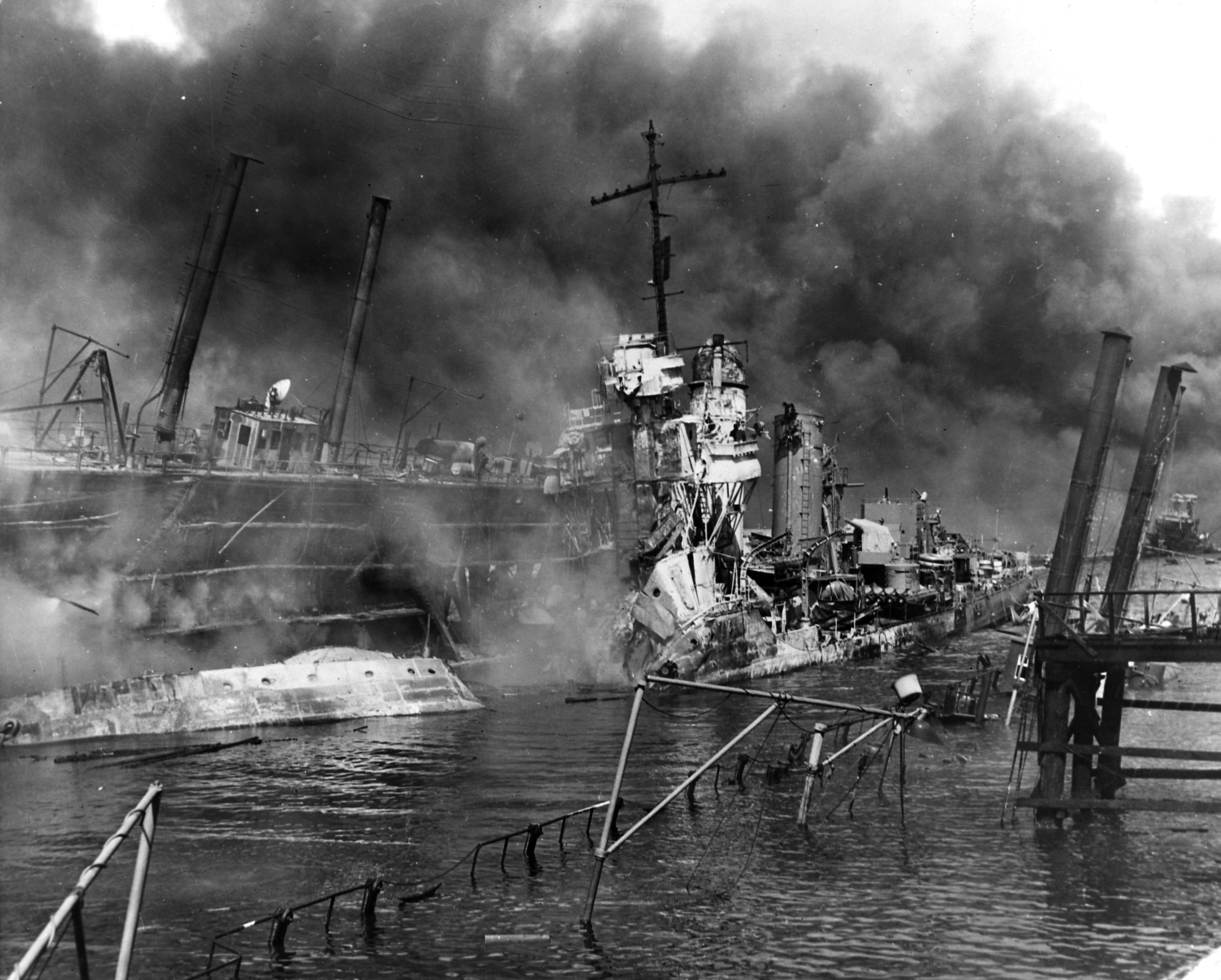 The U.S. Navy destroyer USS Shaw (DD-373) wrecked in floating drydock YFD-2 on December 7, 1941, with fires were nearly out but structure still smoking. Her bow had been blown off by the explosion of her forward magazines, after she was set afire by Japanese dive bombing attacks. In the right distance are the damaged and listing USS California (BB-44) and a dredge. Official U.S. Navy Photograph, National Archives Collection.