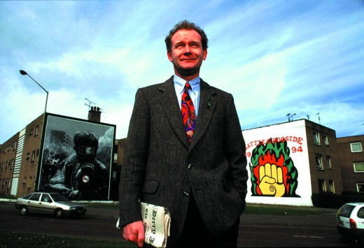 Mc Guinness beside political murals near his home in Derry, April, 1997
