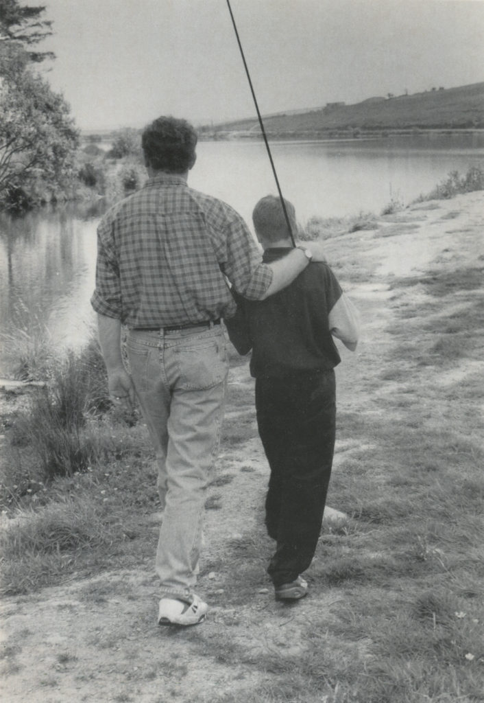 "Martin McGuinness, then vice-president of Sinn Féin, with son fly-fishing, photographed by David Spielman for Irish America in the fall of 1995. Spielman wrote at the time, ""I had read that Martin McGuinness was an avid fisherman who pictures himself on a sea trout farm in the west of Ireland when the Troubles are all over. When I mentioned this to him he invited me to go fishing with him and he brought along his son. We spent several hours together fly-fishing the reservoir north of Derry."""