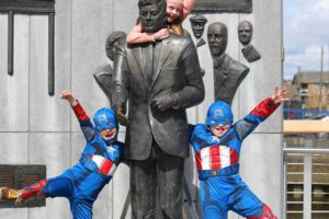 Local children masquerade as patriotic superhero Captain America and pose with the life-sized statue of President John F. Kennedy at the New Ross quayside.