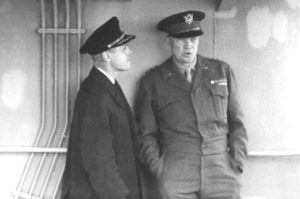 Captain Edmond J. Moran chats with General Eisenhower. Later promoted to Rear Admiral, Moran organized the towing of artificial harbors to the beaches at Normandy, making D-Day landings possible. For his service he was awarded the Legion of Merit, the Croix de Guerre, and the Order of the British Empire.