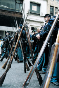 Re-enactors give their muskets a rest while waiting to join the parade.