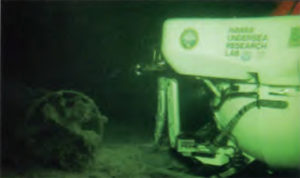 Pisces IV by the stern of the midget submarine.