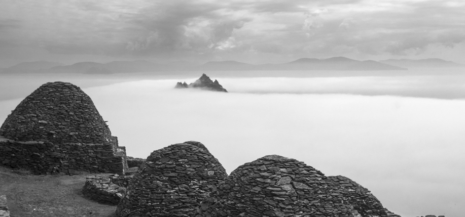Beehive huts on Skellig Michael; Little Skellig peaking out of clouds in background. County Kerry, Ireland. Photo: Chris Ryan.