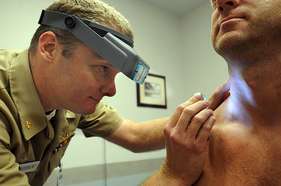 Naval Lt. Cmdr. Stephen Mannino examines a Sailor using a dermatascope and magnifying loops. Photo: Wikimedia Commons