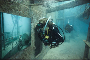 """Divers tour Andreas Franke's exhibition """"The Sinking World"""" in the USS Vandenberg. Photo: Andreas Franke."""