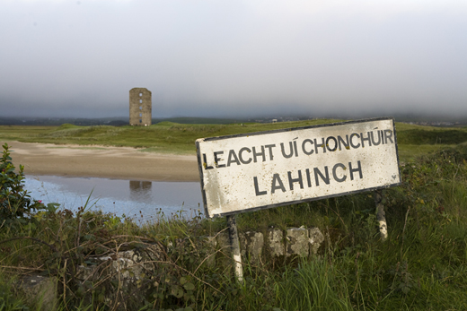 Lahinch town sign in Gaelic and the remains of Dough Castle, Lahinch.