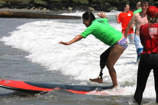 Ana Manciaz, a Wounded Warrior alumna, shows other Warriors how to surf. Photo: Wounded Warrior Project.