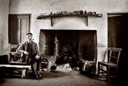Peatcutter beside his fireplace, Co. Galway, 1971.