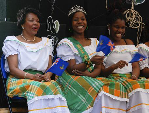 Miss Montserrat, center, with women wearing traditional green, orange, and white Montserratian dresses.