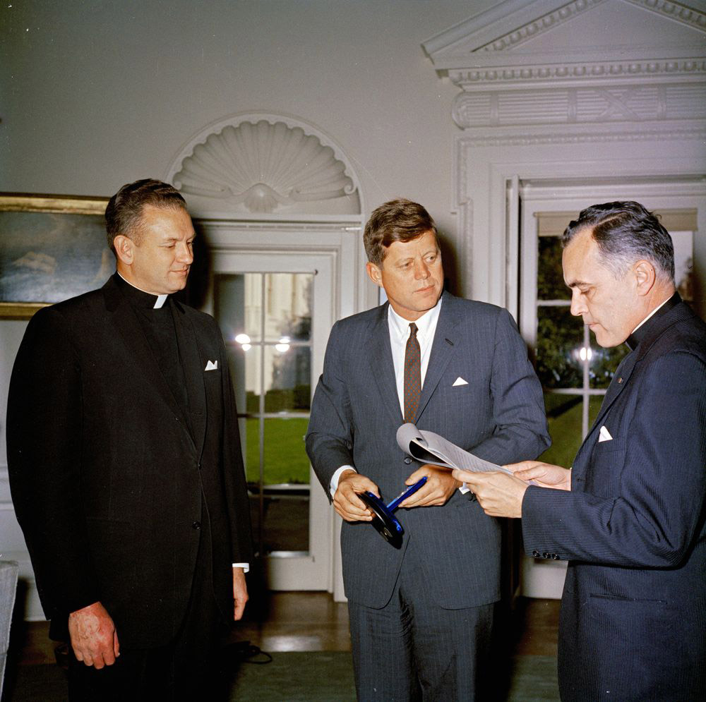 everend Theodore M. Hesburgh (right), president of the University of Notre Dame, delivers remarks at the presentation of the Laetare Medal for 1961 from the University of Notre Dame to President John F. Kennedy. Father Edmund P. Joyce, vice president of the University of Notre Dame, looks on. Oval Office, White House, Washington, D.C. 22 November 1961. (Photo: Photo: Robert Knudsen. JFK  Presidential Library and Museum.)