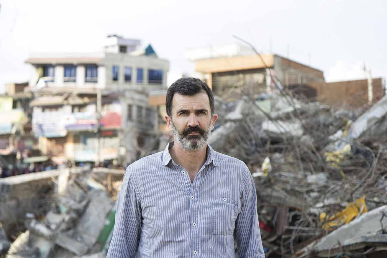 Kieran McConville standing in front of a collapsed building in Kathmandu. Kieran works in the Communications Unit of Concern Worldwide and travels extensively to document the organization's emergency  response and development work around the world. He is originally from Limerick, Ireland and lives in New York City.