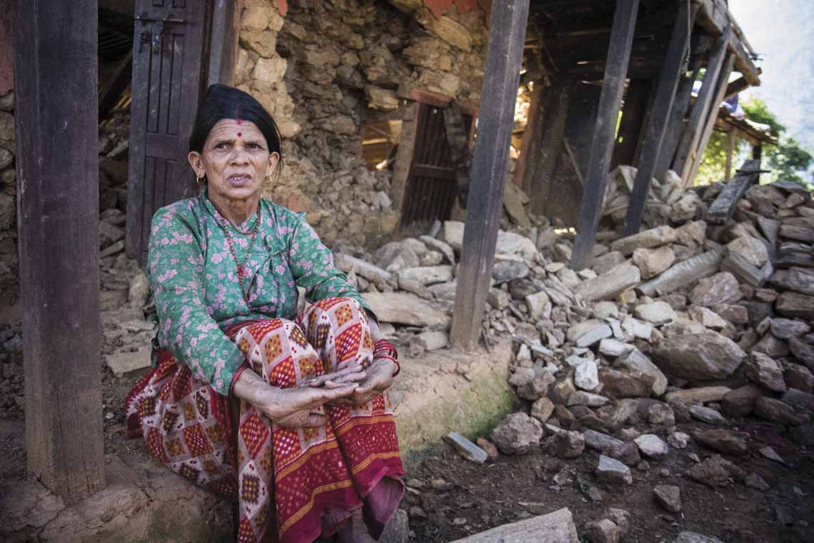 Tulasa Aryal, 58, sits on the porch of her earthquake-ravaged home in Bakrang, a village near the epicenter of the earthquake. A roughly hour drive from Gorkha, Bakrang is among the hardest hit villages in the 7.8-magnitude earthquake that hit Nepal on April 25. Out of 793 houses homes in Bakrang, 515 were completely destroyed.