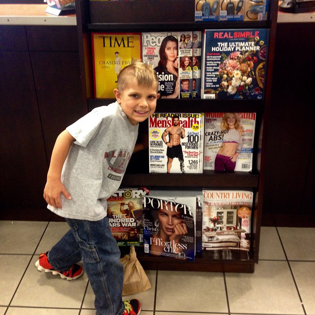 Noah Galloway's son Jack standing in front of a newsstand displaying his dad on the cover of Men's Health. (Photo courtesy Noah Galloway)