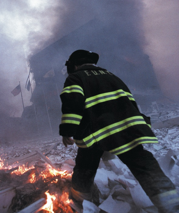 A firefighter walks through the burning rubble as toxic fumes fill the air.