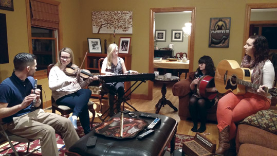 Rehearsal at the home of Rose  Flanagan, herself a former Cherish The Ladies fiddler, are flute player Sean Tierney, a regular guest performer with Girsa, Maeve Flanagan, Emily McShane, Bernadette Flanagan, and Pamela Geraghty.