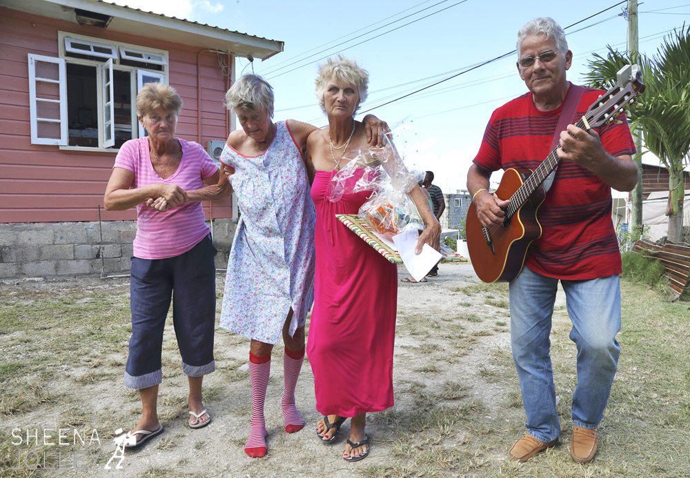 "Erlene Downie being helped back to her own house by daughters Hazel (on left) and Ann (on right) and serenaded by Willie Kerr of The Merrymen band so well known in Barbados for years. Ann is holding the hamper of food and Christmas present given to Erlene on Love Day by Terry Arthur. Terry started the Love Day charity 5 years ago visiting vagrants, homeless and sick but this is their first visit to the ""poor white"" community on the east coast."