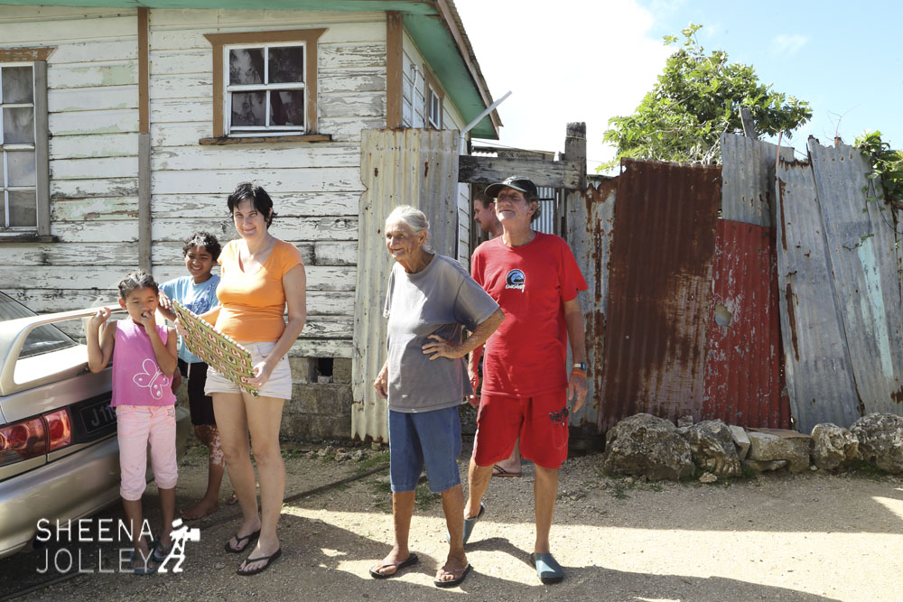 One family all living in one small chattel house. From left Britney, Brent, their mother Carol, her mother and father Louise and Wilson Yearwood. The house is divided into a series of very small rooms and the shower and toilet are outside hidden behind the corrugated iron fencing.