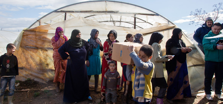 Syrian refugees wait in line for their winter clothes to be distributed by the Concern team at the informal tented settlement in the village of Mohamara, in Akkar, north of Lebanon Wednesday, February 18, 2015. Photographer: Dalia Khamissy