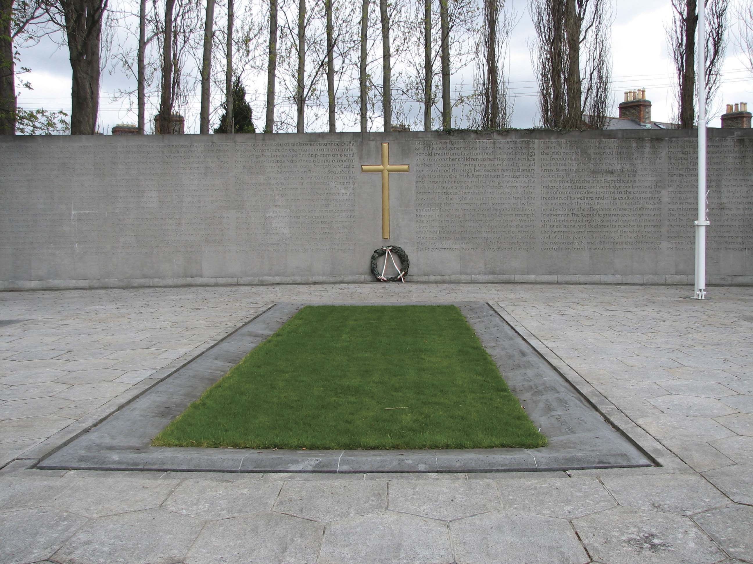 The burial spot of the Leaders of the Rising, in the yard of Arbour Hill prison. The memorial was designed by G.  McNicholl. The  Proclamation of 1916  is inscribed on the wall in both Irish and English.