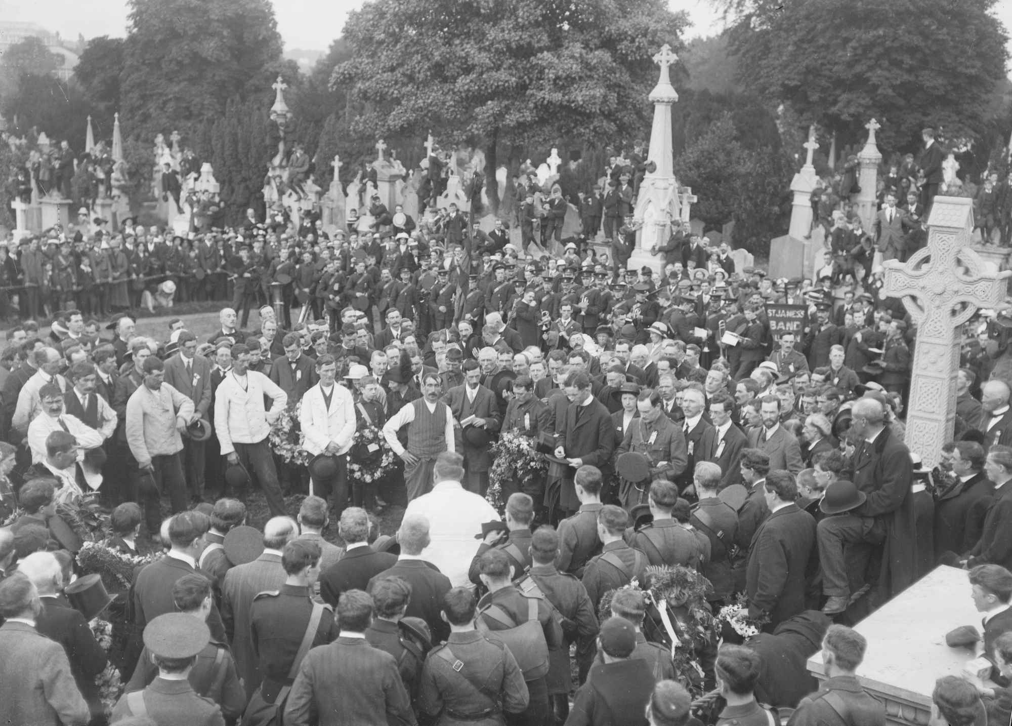 O'Donovan Rossa's funeral at  Glasnevin Cemetery in Dublin, with Pádraig Pearse (standing to the right of the priest, his hat in front of him), John MacBride (to the right of Pearse), and Tom Clarke (three to the right of MacBride, in profile).