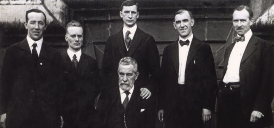 Left to right: Harry Boland, Liam  Mellows, Éamon De Valera, John Devoy (seated), Patrick  McCartan, and Diarmuid Lynch at the Waldorf  Astoria Hotel in New York, June 1919.