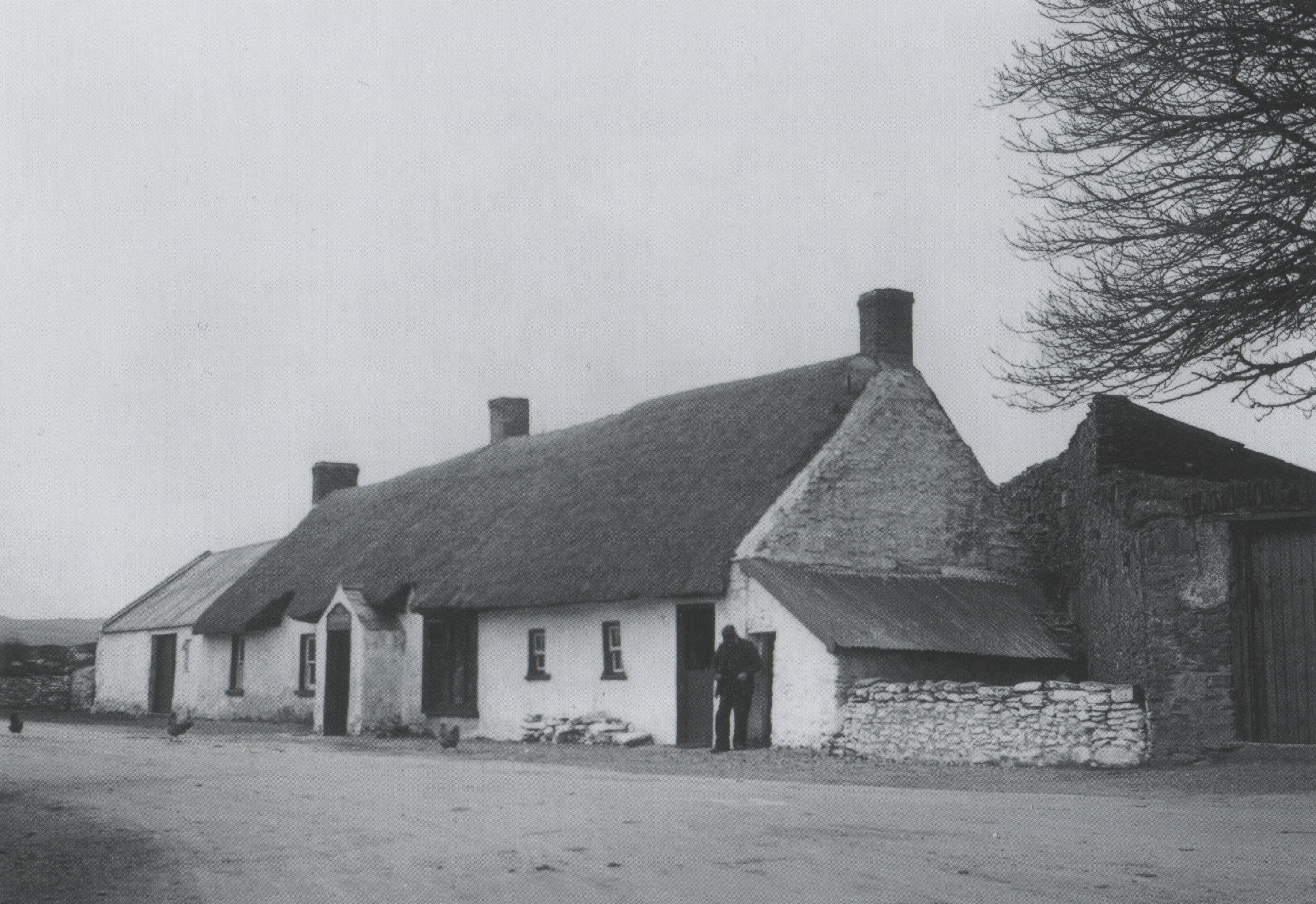 Thatched public house. Tall chimneys and low gables, along with the absence of súgán ropes, indicate that this is an inland location.