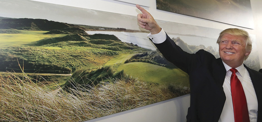 Republican presidential nominee Donald Trump poses at a photo of his golf course in  Doonbeg, Co. Clare.