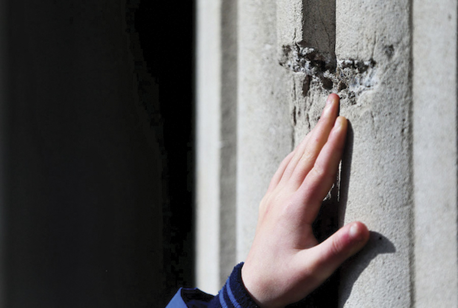 Eamon Heffernan (8) from Limerick touches a bullet hole in the GPO.