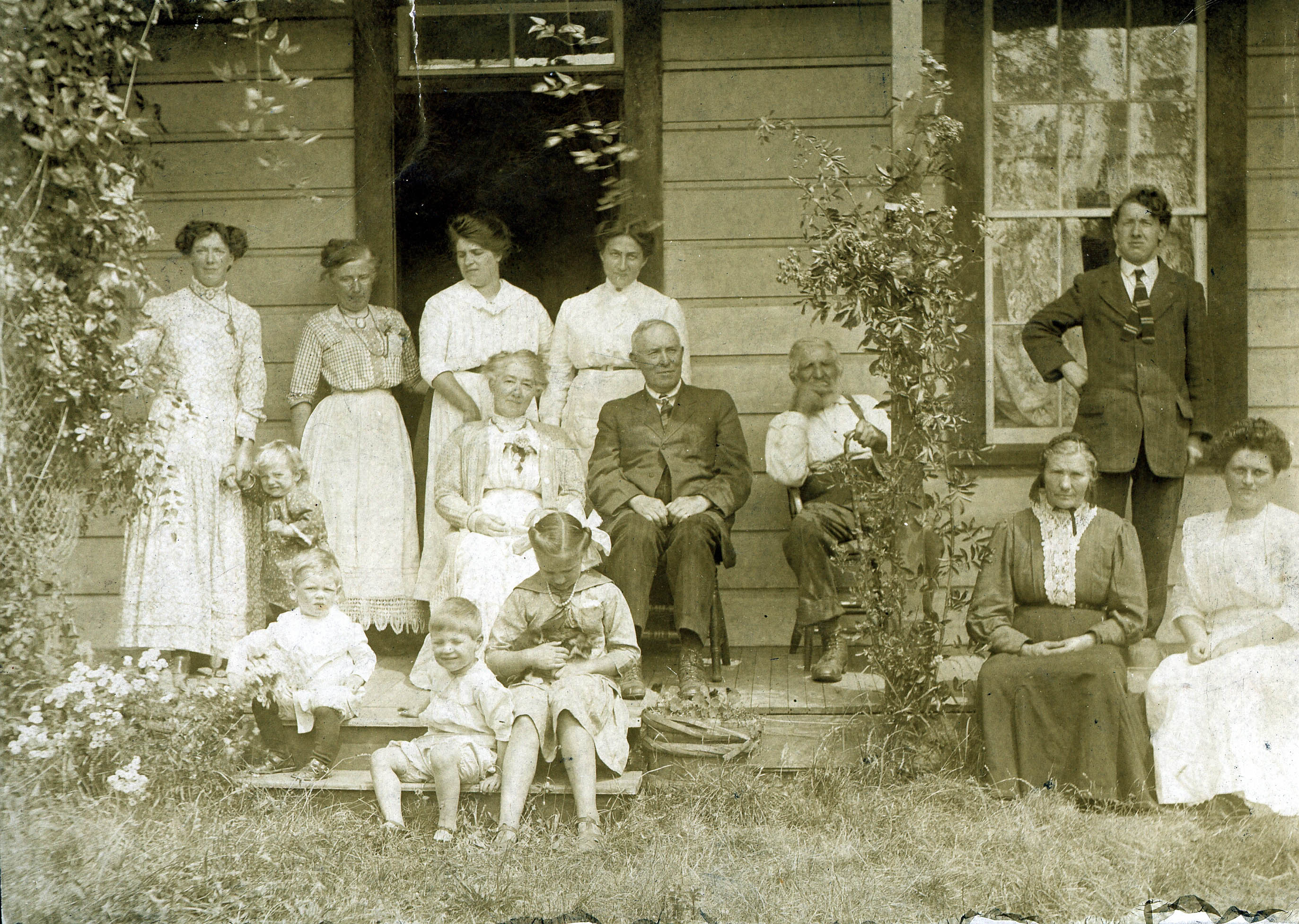 A Ruckle family gathering with friends at the Ruckle homestead, c. 1900. Henry Ruckle is seated left of the post, his wife, Ella Anna, seated to the right. (Photo: Ruckle Family Photographic Collection / Salt Spring Archives)