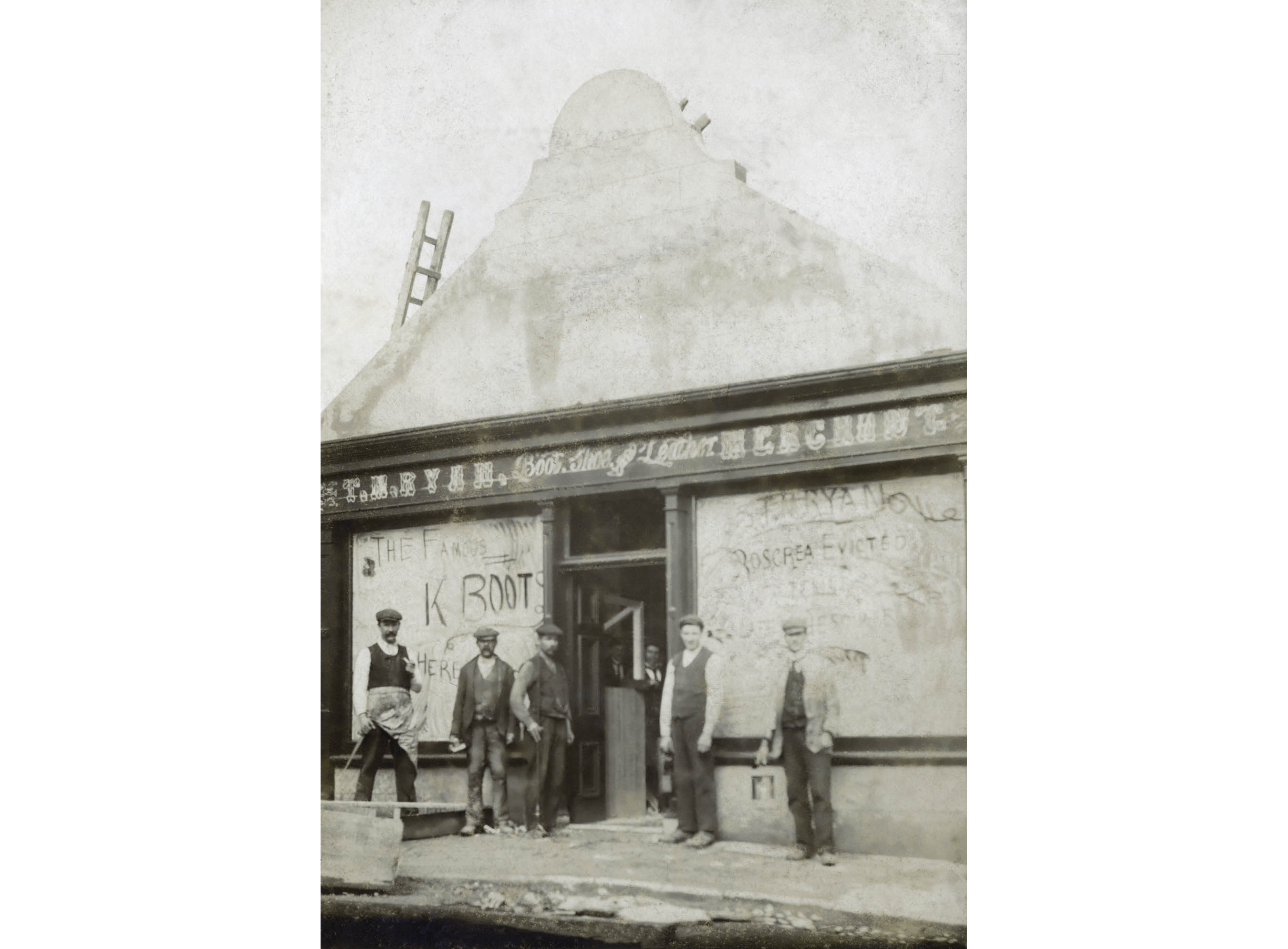 "Men stand in front of a shoe and leather merchant store with boarded up windows. Writing on the right window reads ""T.M.Ryan Roscrea Evicted."" Roscrea, Co. Tipperary, c. 1888."