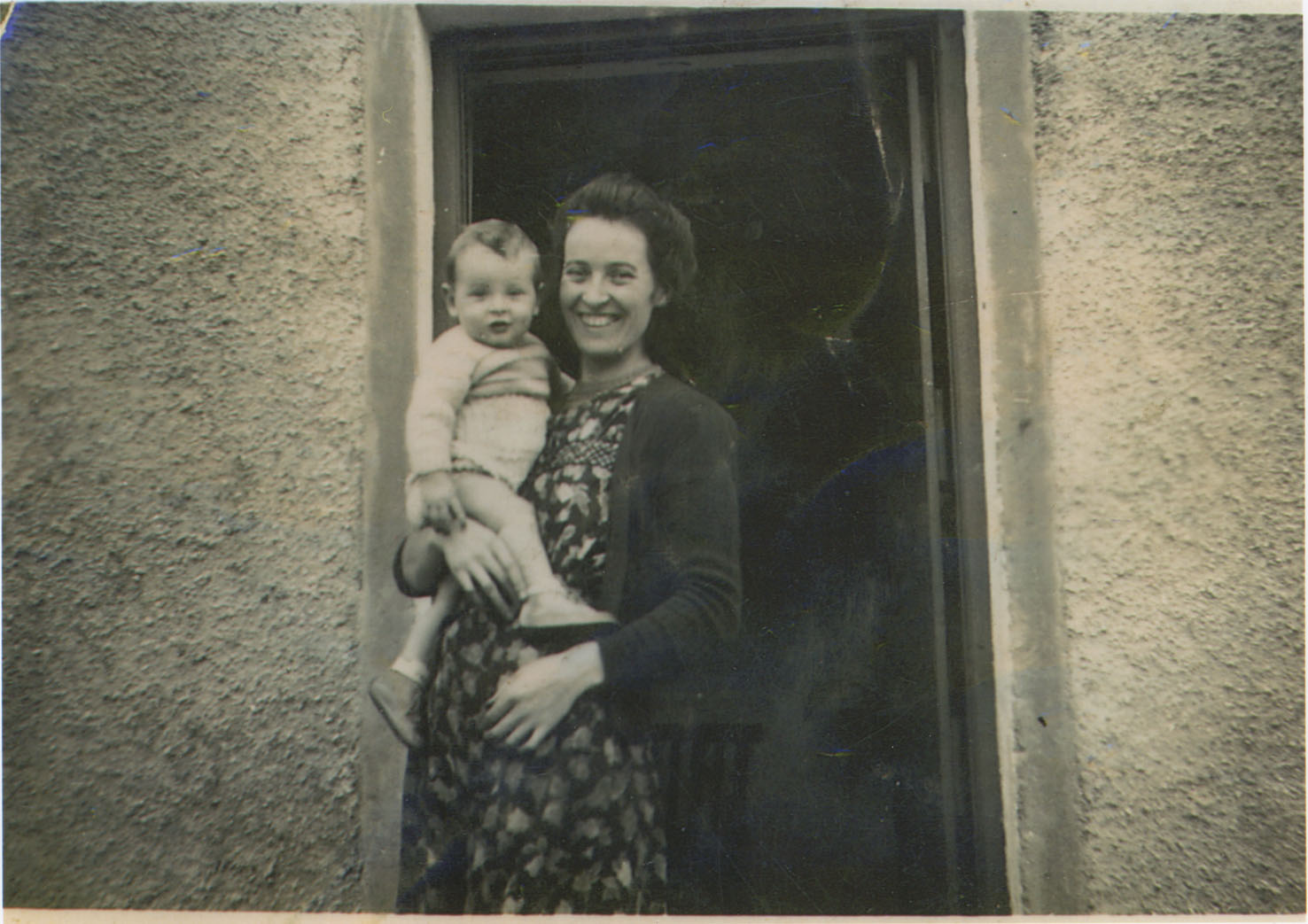 Michael Dowling, held by his mother Meg in front of their thatched cottage home in Knockaderry, County Limerick, 1950.