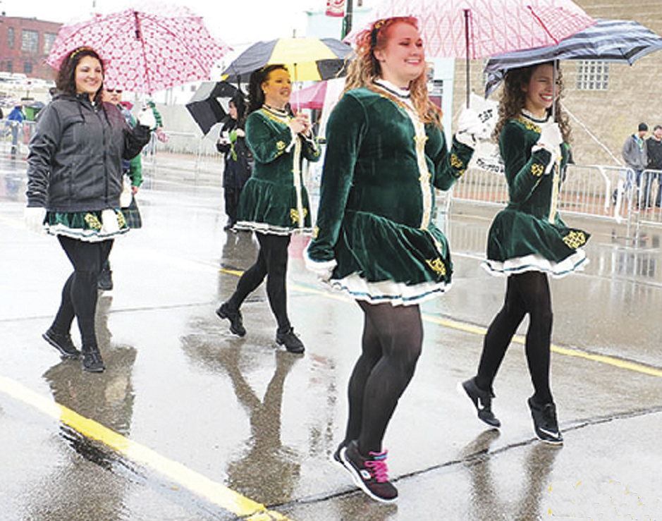 Irish step dancers march on a rainy St. Patrick's Day Parade in Detroit.