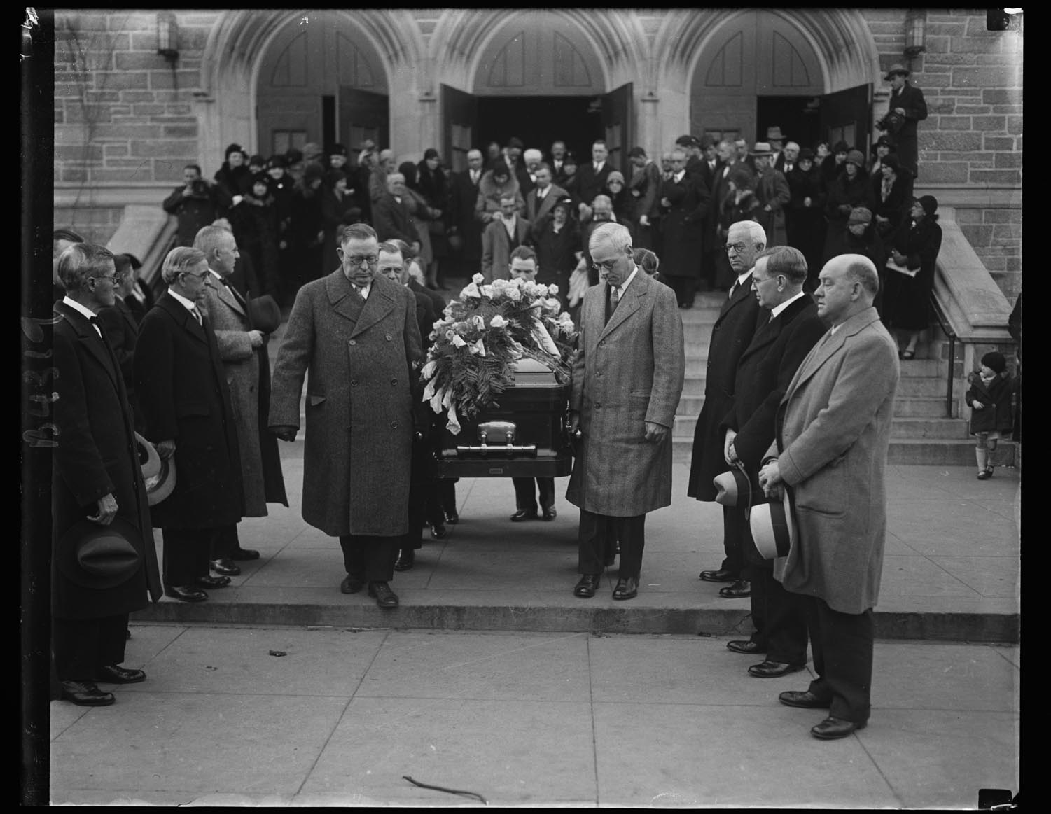 "Men, high in the ranks of labor  circles, take part in the last rites for Mother Jones. At right, William N. Doak, newly  appointed Secretary of Labor. The casket is being borne from St. Gabriel's Catholic Church in Washington, D.C., where services were held, after which the body was sent to Mount Olivet, Illinois,  to be buried beside  five of her ""boys"" slain  in one of the many  labor wars in which  she participated,  December 3, 1930."