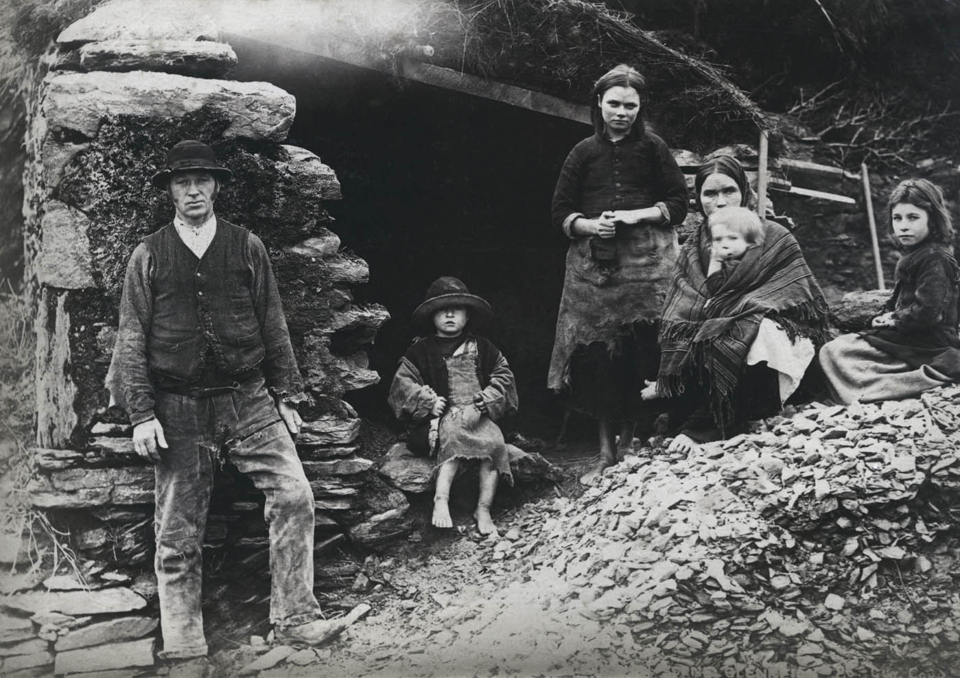 A family at the ruins of their house in Killarney, Co. Kerry, June 1897.