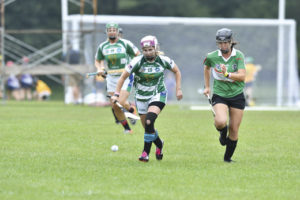 Captain Heather Warren of Coastal Virginia Camogie focuses on winning the ball before a Seattle Gaels camog does.