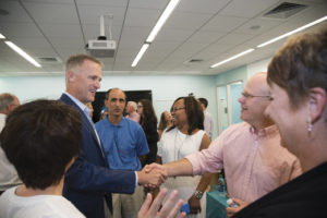Mike greets a patient with a Boston Scientific stent and his wife, along with other members of the team.