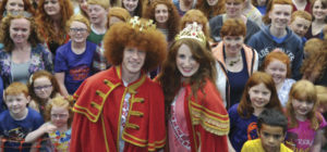 Newly crowned Redhead King and Queen, Alan Reidy and Grainne Keena, pose with a crowd full of red heads at the Irish Redhead Convention, which celebrates everything to do with red hair held in the village of Crosshaven on August 22, 2015 in Cork.