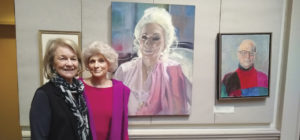 The artist Louise Peabody and singer Judy Collins pose in front of Peabody's portrait of Collins at the Century Club.