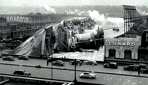 <em>The</em> SS Normandie <em>lies on its side on the Hudson River after a fire aboard the ship.</em>