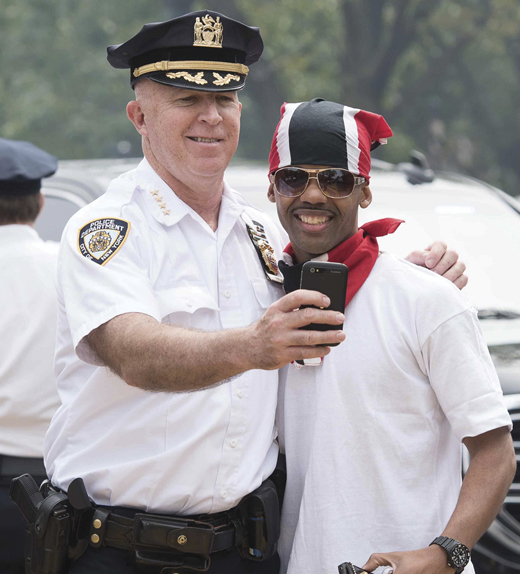 <em>O'Neill takes a photo with a celebrant of the West Indian Day Parade.</em>